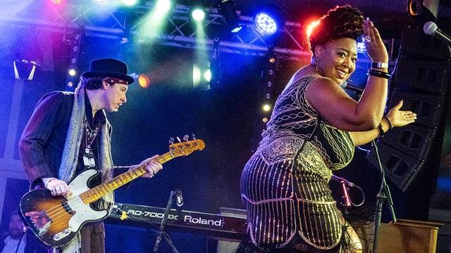 Eine Frau tanzt auf einer Bühne, dahinter spielt ein Mann Gitarre.