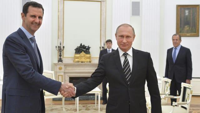 Assad (links) und Putin (rechts) schütteln die Hände
