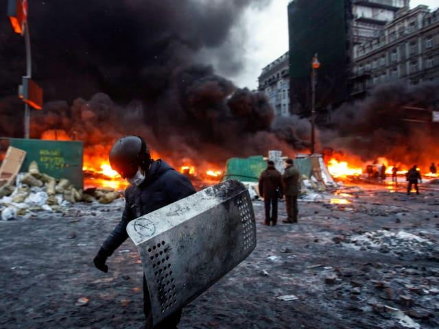 Brennende Barrikaden im Hintergrund, im Vordergrund ein vermummter Demonstrant mit einem von einem Polizisten erbeuteten Schutzschild.