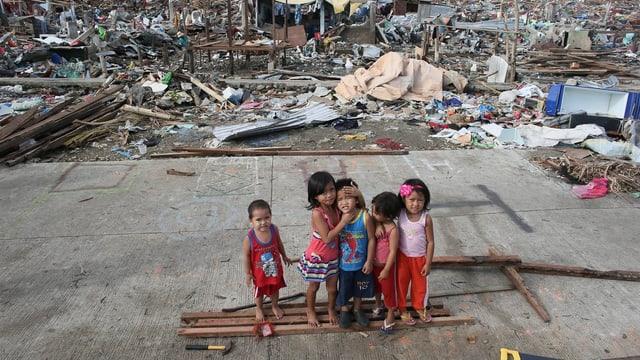 Kinder spielen in den Trümmern.