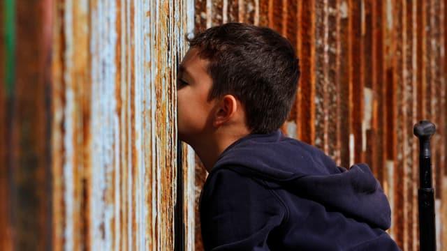 Ein junge spricht durch einen hohen Zaun