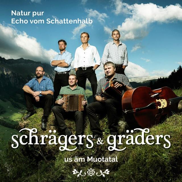 Sechs Männer stehen oder sitzen auf einer Wiese in den Bergen.
