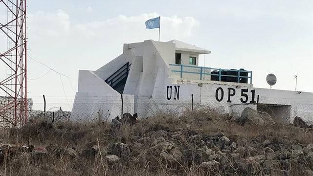 Weissgestrichener Betonbunker. Darauf weht UNO-Flagge. Er ist mit OP 51 angeschrieben.
