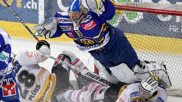 HCD-Goalie Gennoni fällt über zwei SCB-Spieler.