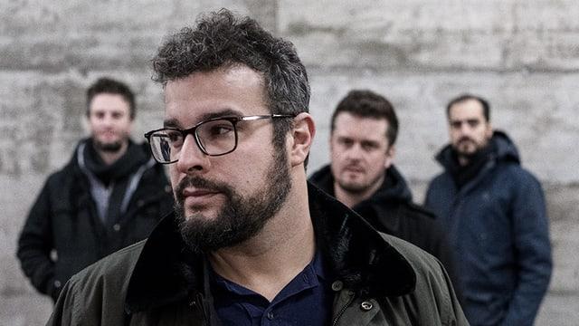 Baze mit Brille im Vordergrund, im hintergrund unscharf drei weitere Männer.