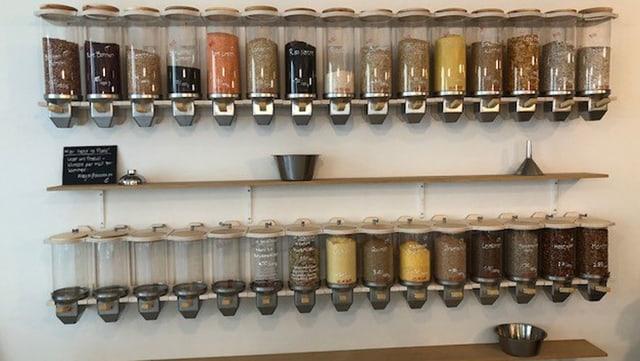 Mit Esswahren gefüllte Glasbehälter an einer Wand
