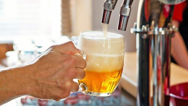 Eine Person hält ein Bierglas in der Hand und füllt es mit Bier vom Zapfhahn.