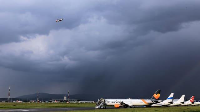 Flugzeuge stehen auf dem Flugplatz, darüber dunkle Regenwolken.