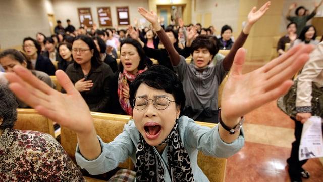 Eine Frau mit geschlossenen Augen streckt beide Arme in die Luft und betet mit offenem Mund.