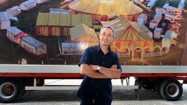 Mann vor einem Zirkuswagen