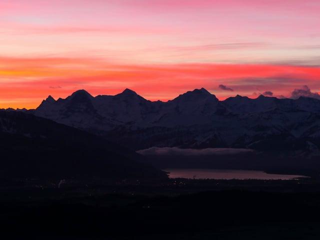 Eine dunkle Bergkette liegt unter einem orange bis violett gefärbten Himmel.