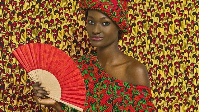 Dunkelhäutige Frau in rot-grüün gemustertem Kleid, der Hintergrund ist im gleichen Muster, aber gelb-rot.