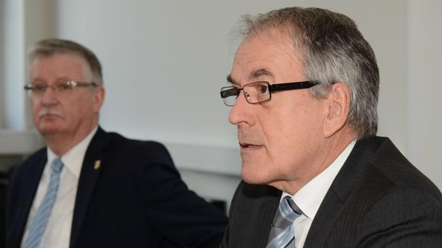 Zwei Männer in Anzug und mit Brillen sitzen an einem Besprechungstisch