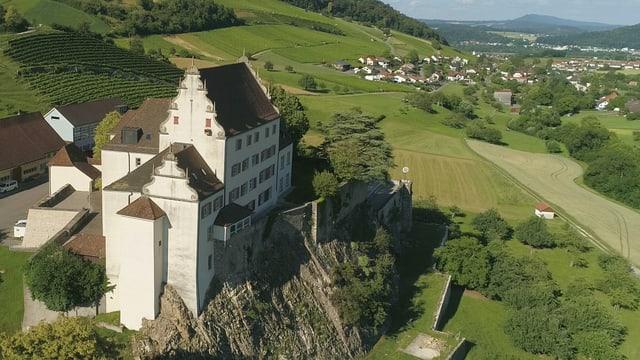 Luftaufnahme einer Schlossanlage auf einem Felsen, eingebettet in einer hügeligen Landschaft.
