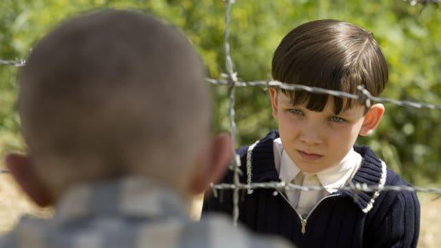 Ein Junge steht vor einem Zaun, hinter welchem ein anderer Junge sitzt.
