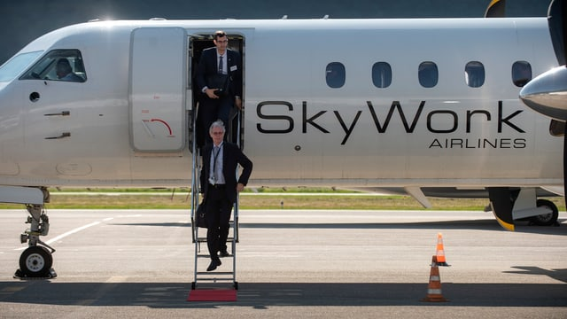 Flugzeug, zwei Personen steigen aus