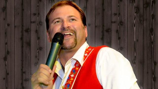 Ein Sänger mit rotem Gilet über einem weissen Hemd.