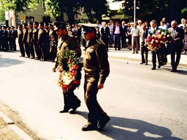 Zwei Soldaten in Uniform tragen eine Blumenkranz. Dahinter weitere Soldaten in einer Reihe.