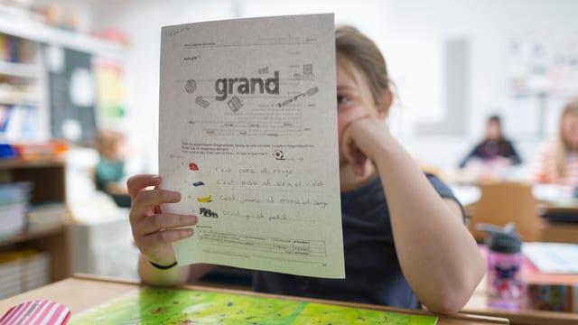 Kind mit Arbeitsblatt in der Hand