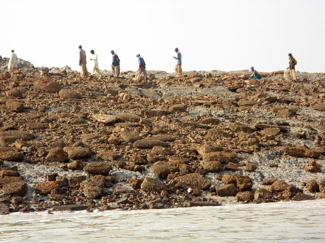 Vereinzelte Menschen laufen auf einer Insel, auf ihr liegen bräunliche Steine.