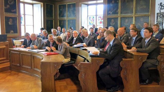 Ratssaal mit Parlamentariern, die in Bankreihen sitzen.