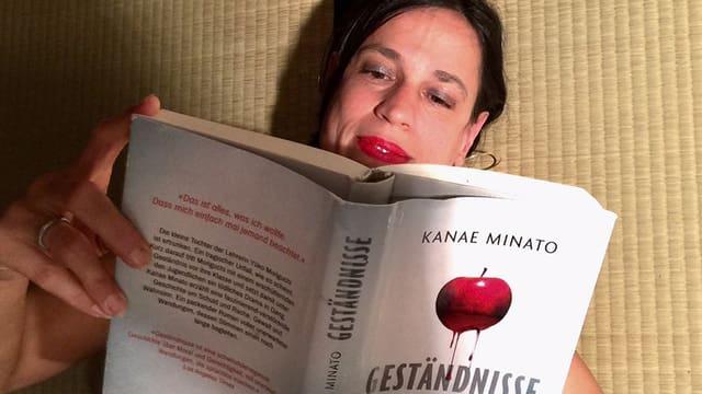 Annette liegt auf einer Tatami-Matte und hält den Thriller «Geständnisse» von Kanae Minato in den Händen