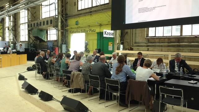 Menschen sitzen in einer Halle an einem langen Tisch, auf einer Leinwand wird das Diskussionsthema gezeigt.