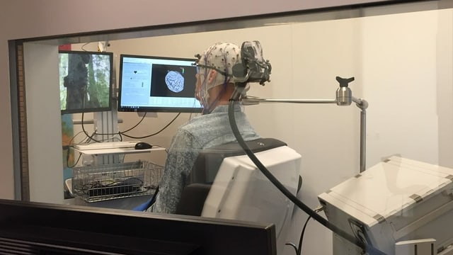 Mann in einem Forschungslabor. Er trägt eine Mütze, an der Kabel befestigt sind. Auf einem Bildschirm ist ein Hirn zu sehen.