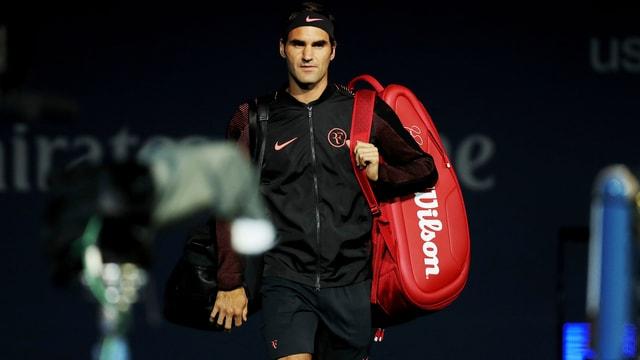 Roger Federer betritt aus dem Dunkeln schreitend den Court.