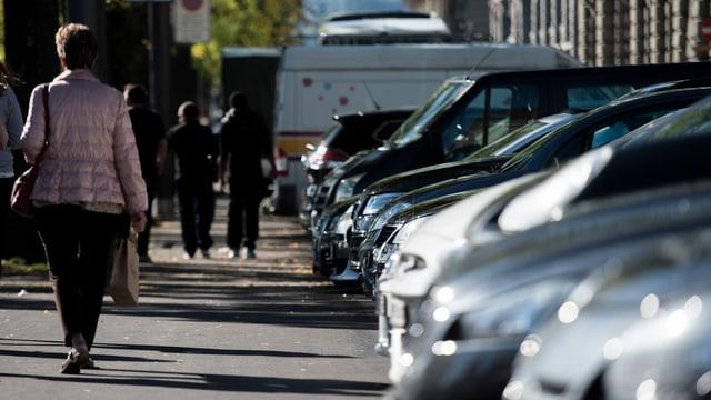 Autos aufgereiht in ihren Parkplätzen, daneben läuft eine Fussgängerin auf dem Trottoir an ihnen vorbei.