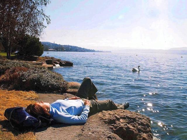 Ein Frau, am Ufer des Zürichsees, lässt sich von der Märzsonne verwöhnen.