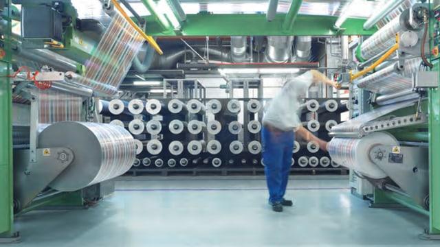 Ein Arbeiter steht an einer grossen Folienrolle.