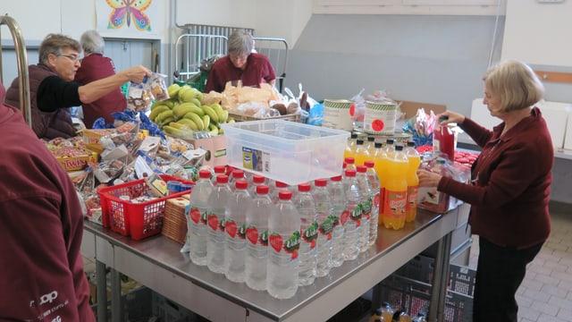 Frauen haben auf einem Tisch viele Lebensmittel gestappelt