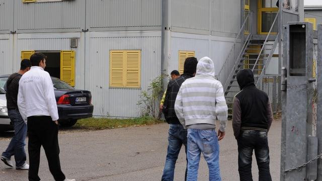 Umens giuvens davant in center d'aquirents d'asil.