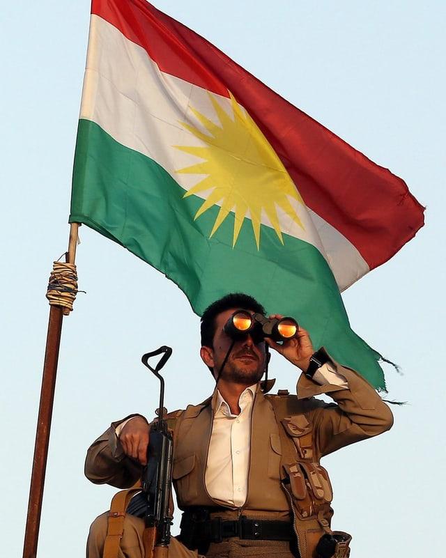 Ein Peschmerga-Kämpfer mit Sturmgewehr und Feldstecher vor einer Flagge Kurdistans.