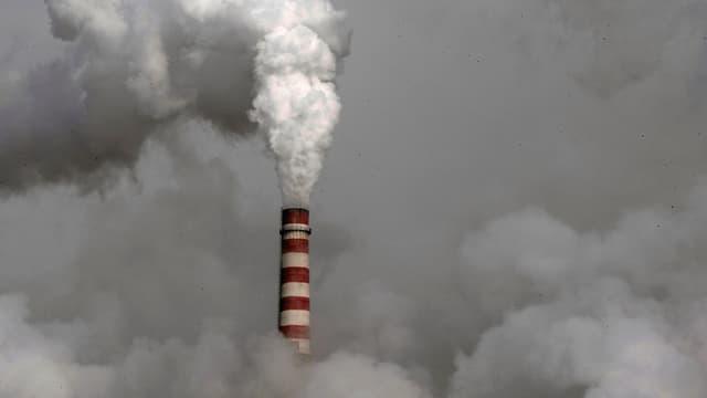 Aus einem rot-weiss gestreiften Schornstein kommt Rauch. Ganzer Himmel in Rauch gehüllt.