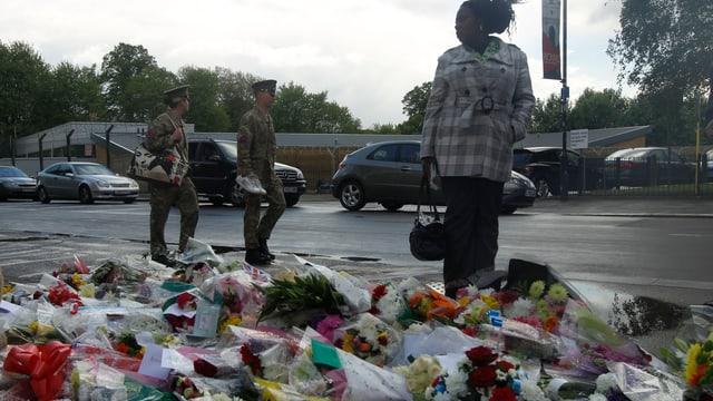 Menschen stehen vor Blumen, wo der britische Soldat ermordet wurde.