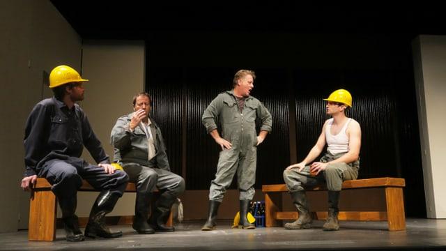 Szene in einem Landtheater: Arbeiter mit gelben Schutzhelmen stehen und sitzen auf der Bühne.