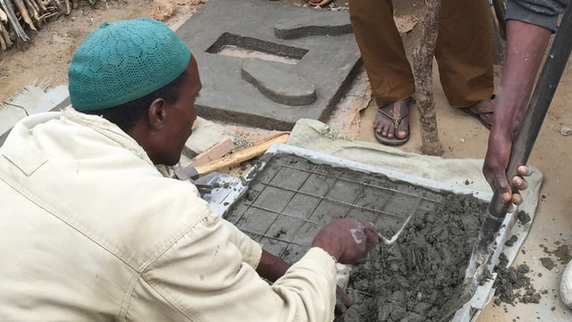 Ein paar Männer bauen eine Latrine in einem afrikanischen Dorf.