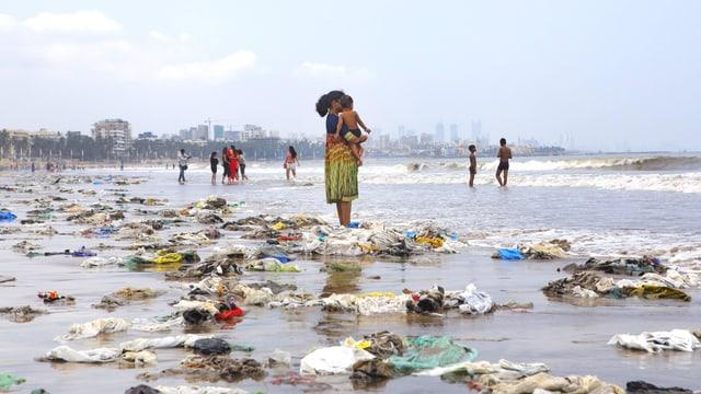 Eine Frau steht am Strand - viel Plastik wurde angespühlt, leere Flaschen, vor allem Plastiksäcke.