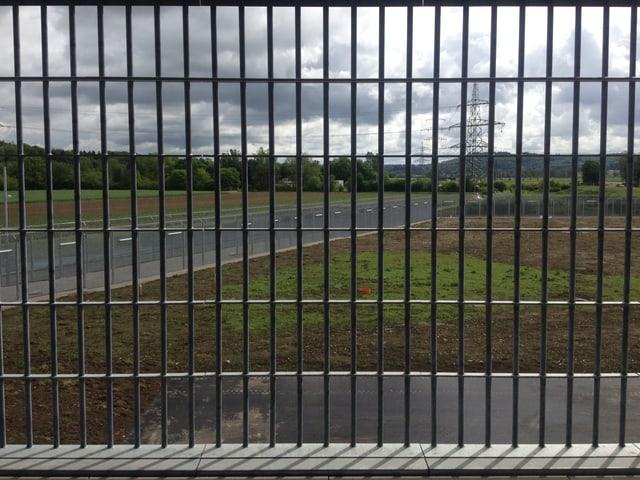 Blick durch Gitterstäbe in den Gemüsegarten des Gefängnisses