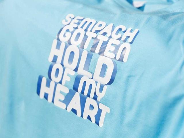 Auf einem hellblauen T-Shirt steht: Sempach gotten hold of my heart.