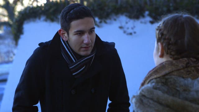 Cem in einem Park wie er mit Meret redet.