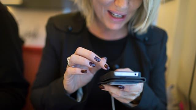 Eine Frau bedient ihr Handy.
