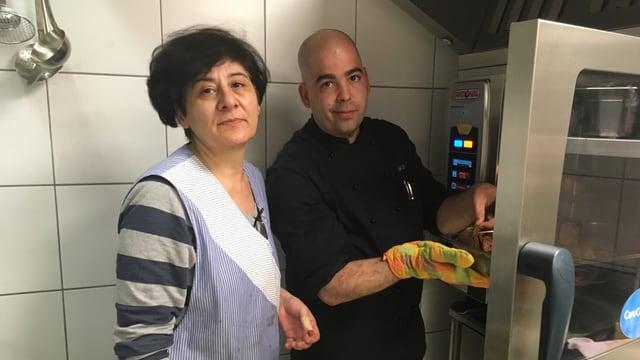 Eine kurdische Frau und ein männlicher Koch werken in einer Küche.