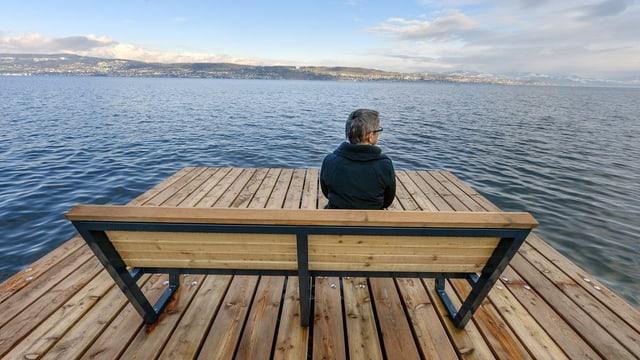 Ein Mann sitzt auf einer Holzbank am See.