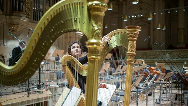 Eine Harfinistin stimmt ihr Instrument in leerem Orchestersaal