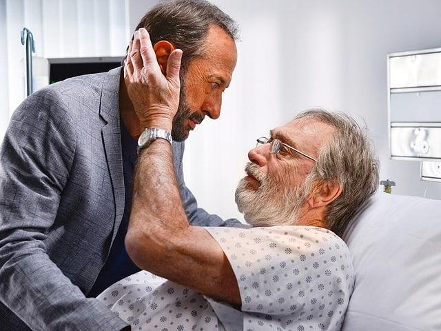 Ein Mann im Spitalbett umarmt einen Besucher.