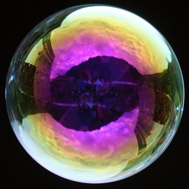 Ein grosse Seifenblase spiegelt die Farben des Umgebungslichtes.