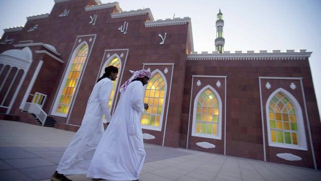 Zwei Männer spazieren an einer Moschee vorbei.